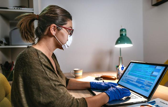 """<span class=""""caption"""">Filing taxes during coronavirus times.</span> <span class=""""attribution""""><a class=""""link rapid-noclick-resp"""" href=""""https://www.gettyimages.com/detail/photo/woman-filling-online-tax-form-wearing-face-mask-and-royalty-free-image/1215490527?adppopup=true"""" rel=""""nofollow noopener"""" target=""""_blank"""" data-ylk=""""slk:Drazen/ E+ via Getty Images"""">Drazen/ E+ via Getty Images</a></span>"""