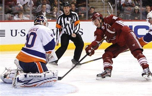 Phoenix Coyotes' Shane Doan (19) scores a goal against New York Islanders' Evgeni Nabokov, left, of Russia, as referee Brad Meier looks on during the second period in an NHL hockey game on Saturday, Jan. 7, 2012, in Glendale, Ariz. (AP Photo/Ross D. Franklin)
