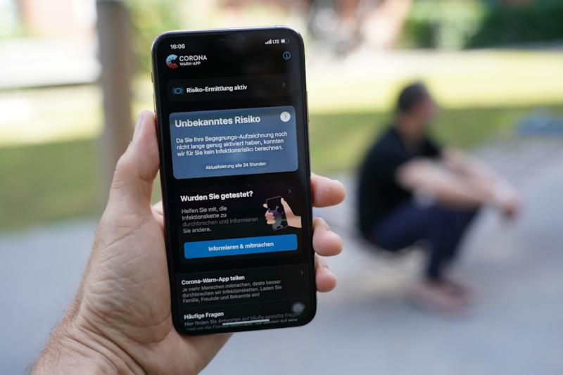 """BERLIN, GERMANY - JUNE 16: The photographer holds an Apple iPhone showing the newly-released """"Corona-Warn-App"""" developed by the German government for tracing Covid-19 infections during the coronavirus pandemic on June 16, 2020 in Berlin, Germany. The app has gone through a careful vetting process in order to stay within the bounds of Germany's tight laws and norms on private data protection. By using a de-centralized system of data retention it will inform users should they come in contact with others who become confirmed Covid-19 infection cases. (Photo by Sean Gallup/Getty Images)"""