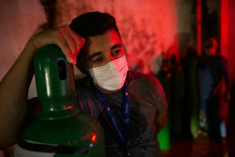 A man holds an oxygen tank in the Brazilian city of Manaus, Amazonas State, on January 15, 2021; the Covid-19 pandemic has hospitals there near the breaking point, with beds full and oxygen supplies running out