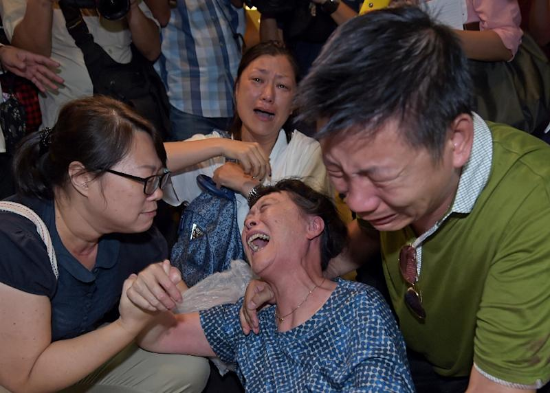 Relatives of a Chinese tourist killed in a bomb blast outside a religious shrine grieve after identifying the body at the Institute of Forensic Medicine in Bangkok on August 18, 2015 (AFP Photo/Ponrchai Kittwongsakul )