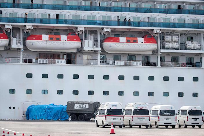 Image: A military vehicle is attached to a gate of the Diamond Princess cruise ship at the Daikaku Pier Cruise Terminal in Yokohama port