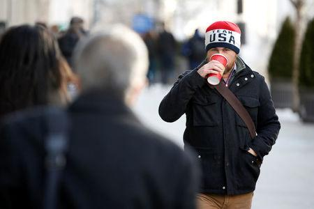 A commuter sips coffee as he walks through record setting cold on his way to work in Washington, U.S., January 3, 2018.   REUTERS/Joshua Roberts