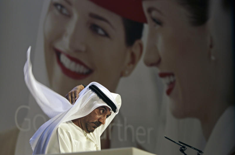 Sheik Ahmed bin Saeed Al Maktoum, Emirates' chairman and CEO, fixes his Ghutra, a traditional men's head scarf, during a news conference in Dubai, United Arab Emirates, Thursday, May 8, 2014. The parent company of the Middle East's biggest airline, Emirates, posted an annual profit Thursday of $1.1 billion as it enjoyed a dip in fuel costs and boosted capacity with the addition of two dozen new planes. (AP Photo/Kamran Jebreili)