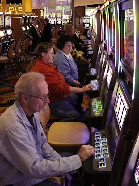 Area resident Jerry Franklin, bottom left, celebrates his 56th birthday by joining other gamblers at the slot machines as the Hollywood Casino Columbus opens on Monday Oct. 8, 2012, in Columbus, Ohio. The $400 million Hollywood Casino Columbus is expected to draw 3 million visitors annually. (AP Photo/Kantele Franko.)