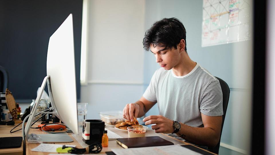A young man eats lunch at his desk in the office.