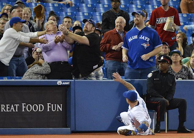 Toronto Blue Jays third baseman Brett Lawrie slides against the wall as fans bobble a Baltimore Orioles foul ball during the second inning of a baseball game in Toronto on Friday, Sept. 13, 2013. (AP Photo/The Canadian Press, Nathan Denette)