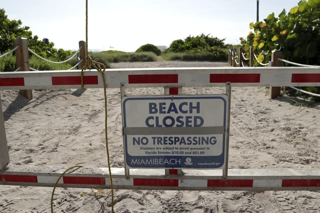 A sign at a closed entrance to the beach in the South Beach neighbourhood of Miami Beach, Florida