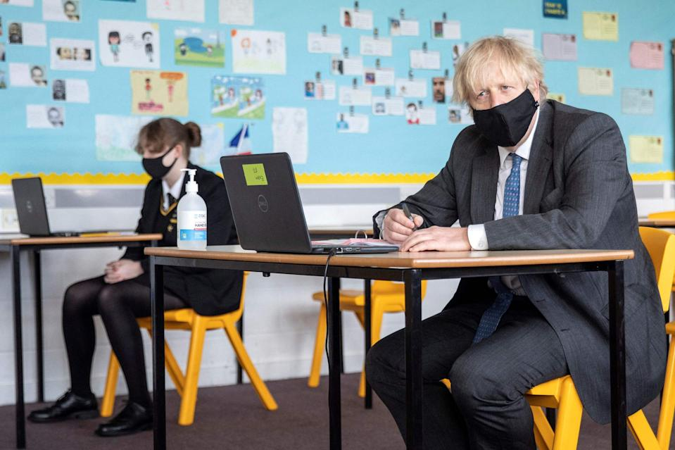 <p>Boris Johnson, wearing a face covering, sits in front of a laptop computer as he takes part in an online lesson during his visit to Sedgehill School</p> (POOL/AFP via Getty Images)