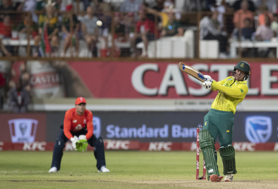 South Africa's captain Quinton de Kock plays a shot as England's Jos Buttler watches on during the 2nd T20 cricket match between South Africa and England at Kingsmead stadium in Durban, South Africa, Friday, Feb. 14, 2020. (AP Photo/Themba Hadebe)