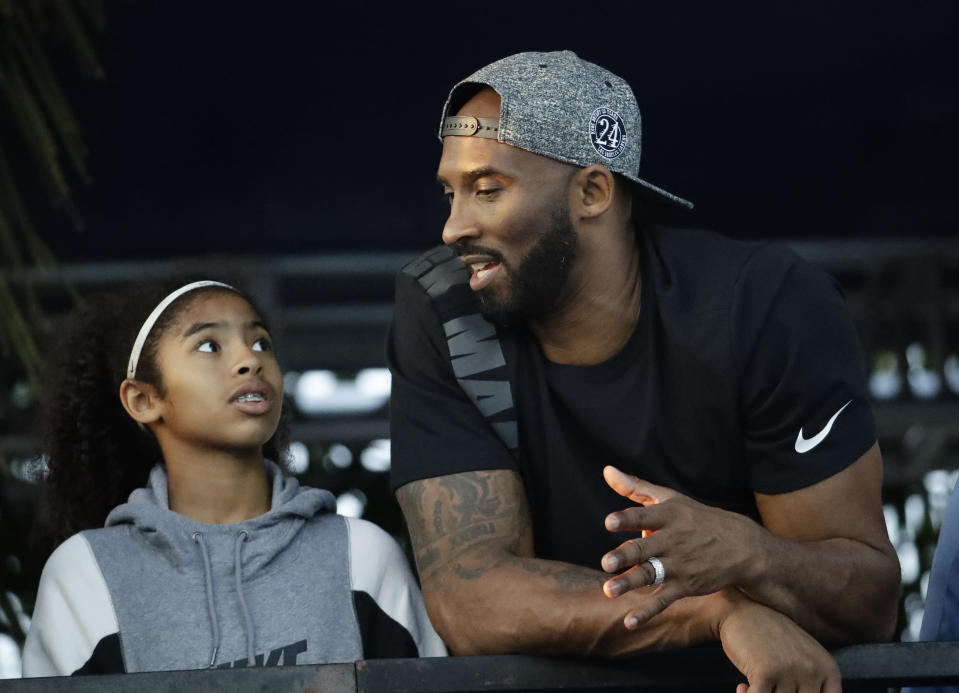 FILE - In this July 26, 2018, file photo, former Los Angeles Laker Kobe Bryant and his daughter Gianna watch the U.S. national championships swimming meet in Irvine, Calif. Federal safety officials are expected to vote Tuesday, Feb. 9, 2021, on what likely caused the helicopter carrying Kobe Bryant, his 13-year-old daughter and seven others to crash into a Southern California hillside last year, killing all aboard. (AP Photo/Chris Carlson, file)