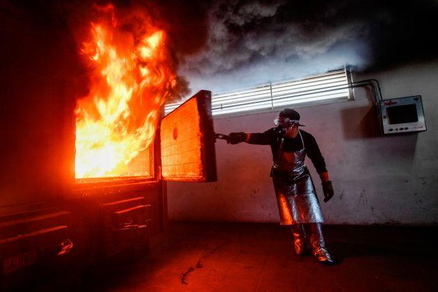 Cremating a single corpse usually takes between two and three hours and releases almost 600 pounds of carbon dioxide. In this January 2021 photo, a crematorium employee in Mexico closes a cremation oven during the cremation of a COVID-19 victim. (Photo: PEDRO PARDO/Getty Images)