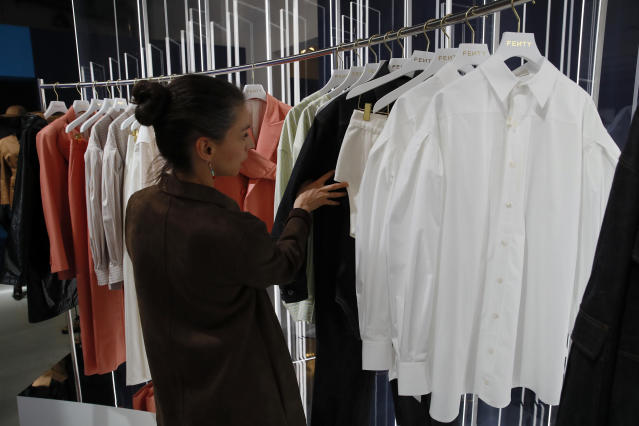A woman looks at creations by Rihanna as she unveils her first fashion designs for Fenty at a pop-up store in Paris, France, Wednesday, May 22, 2019. Singer Rihanna is the first black woman in history to head up a major Parisian luxury house, and the collection, named after the singer turned designer's last name, comprises of ready-to-wear, footwear, accessories, and eyewear and is available for sale Paris' Le Marais area from Friday and will debut online May 29. (AP Photo/Francois Mori)