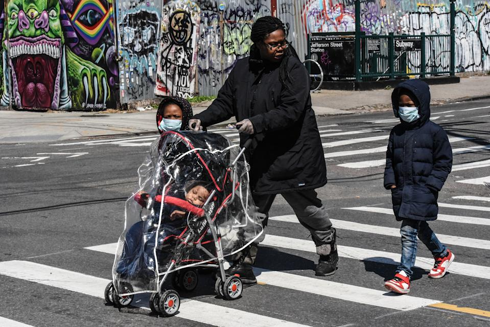 A new study from the CDC has found a higher prevalence of COVID-19 cases among young boys than girls. Here, a child wears a protective masks while standing on a corner in Brooklyn. (Photo: Stephanie Keith/Getty Images)