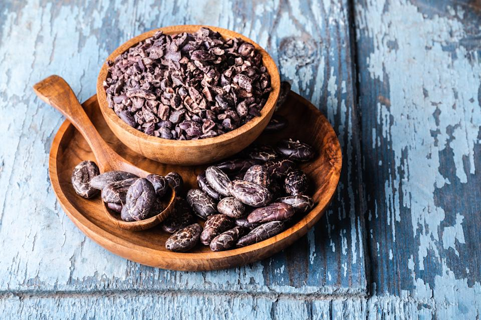 Organic raw dry cocoa beans, nibs in wooden bowls on blue old rustic background close-up.