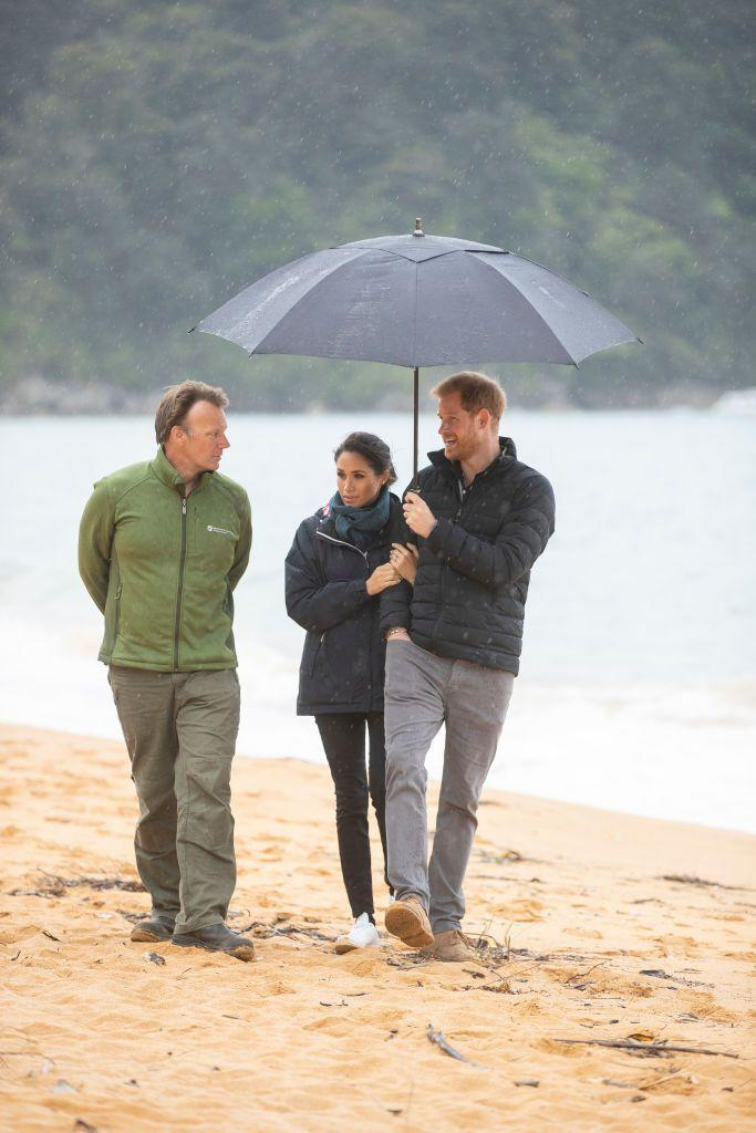 <p>Meghan and Harry walked arm-in-arm while the Duke held an umbrella over the couple as they strolled in the Abel Tasman National Park with the area manager in New Zealand.</p>