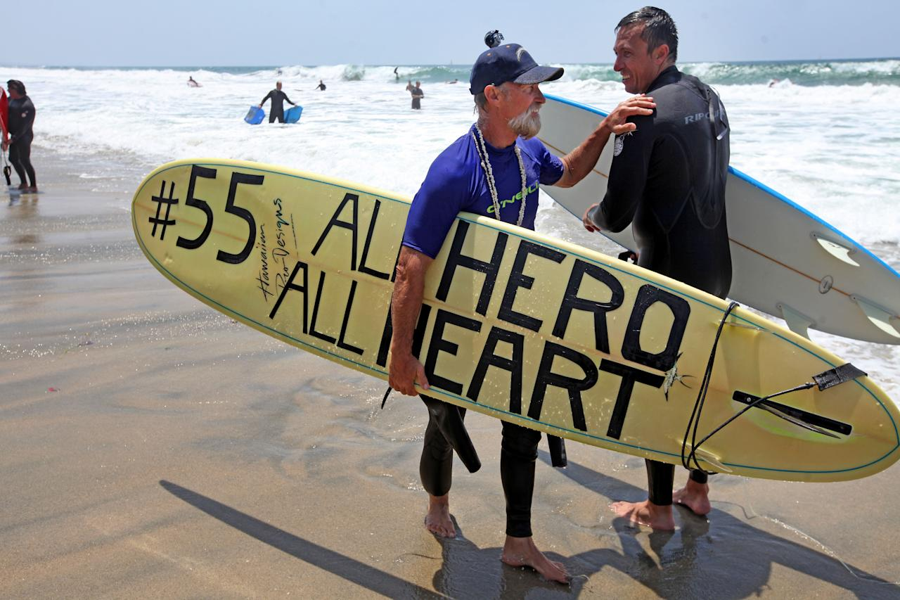 "OCEANSIDE, CA - MAY 6: Fred Hodges shows a surfboard he decorated during a ""paddle-out"" in honor of NFL star Junior Seau on May 6, 2012 in Oceanside, California.  Seau, who played for various NFL teams including the San Diego Chargers, Miami Dolphins and New England Patriots was found dead in his home on May 2nd of an apparent suicide.  Family members have decided to donate his brain for research on links between concussions and possible depression. (Photo by Sandy Huffaker/Getty Images)"