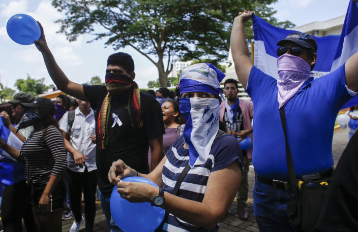 Students, many hiding their identify for fear of being identified and later targeted by security forces or government supporters, protest inside the Central American University (UCA) where security forces cannot legally enter, as they demand the release of all political prisoners in Managua, Nicaragua, Tuesday, June 18, 2019, the last day of a 90-day period for releasing such prisoners which was agreed to during negotiations between the government and opposition. Nicaragua's government said Tuesday that it has released all prisoners detained in relation to 2018 anti-government protests, though the opposition maintains that more than 80 people it considers political prisoners are still in custody. (AP Photo/Alfredo Zuniga)