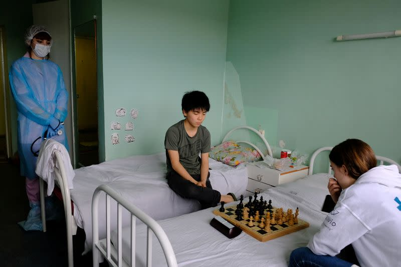 Chess players from France look at the board during a game at a hospital in Murmansk