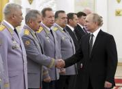 Russian President Vladimir Putin shakes hands with Defense Minister Sergei Shoigu, second left, as he greets senior military officers during a meeting in Moscow, Russia, Wednesday, Nov. 6, 2019. Putin said Russia's new weapons have no foreign equivalents but he insists the country will not use them to threaten anyone. (Mikhail Klimentyev, Sputnik, Kremlin Pool Photo via AP)