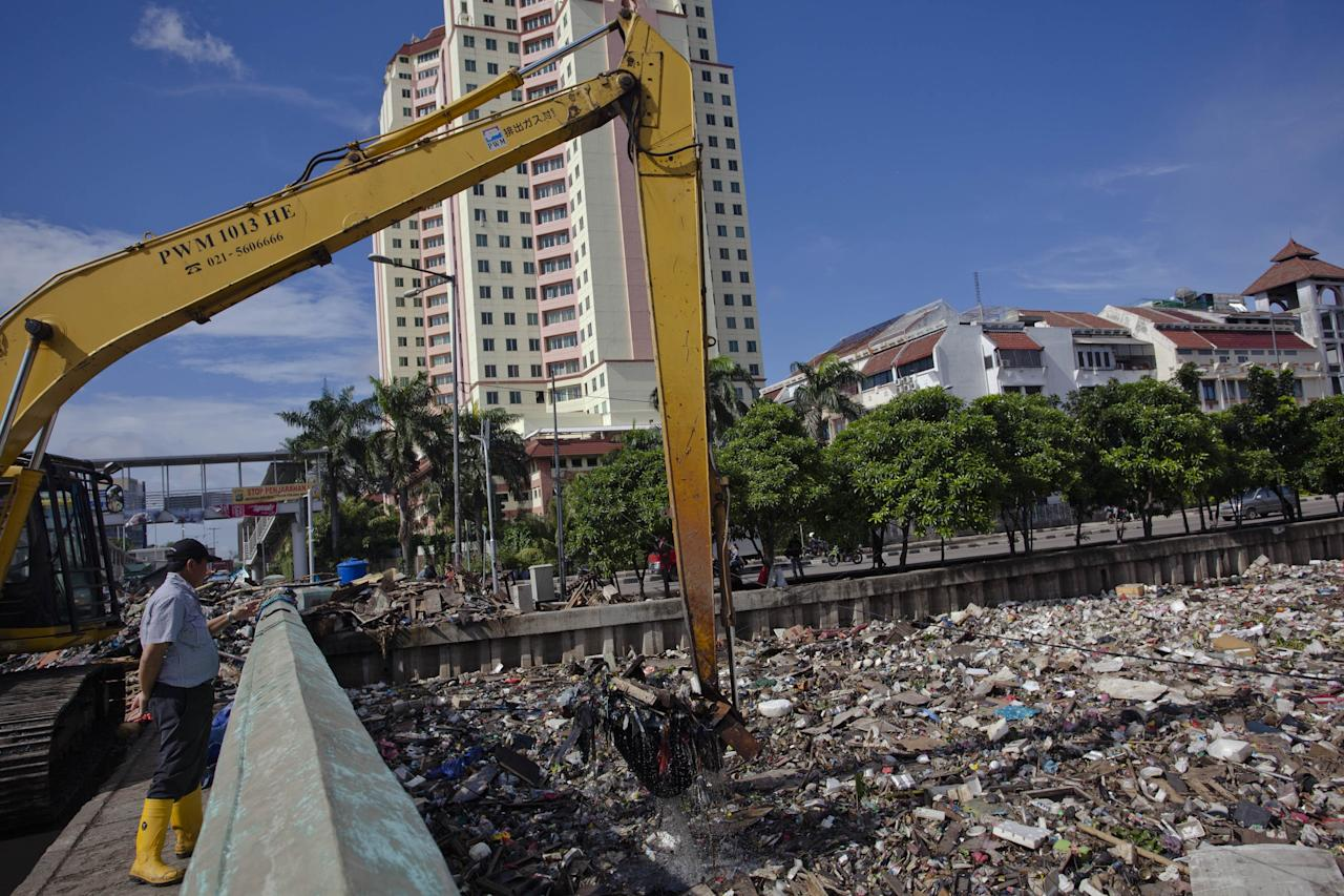 JAKARTA, INDONESIA - JANUARY 26:  Workers used excavator to clean up waste that was piled up by the flood at Pakin river in North Jakarta on January 26, 2013 in Jakarta, Indonesia. With heavy rain forecast for January 26-28, Indonesian authorities have organised the use of generators and cloud-seeding measures to defuse rain-laden clouds to help prevent further flooding of Jakarta, following last week's floods which claimed the lives of 32 people.  (Photo by Ulet Ifansasti/Getty Images)