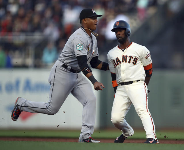 Miami Marlins' Starlin Castro, left, tags out San Francisco Giants' Andrew McCutchen in a rundown between first and second base in the first inning of a baseball game Monday, June 18, 2018, in San Francisco. (AP Photo/Ben Margot)