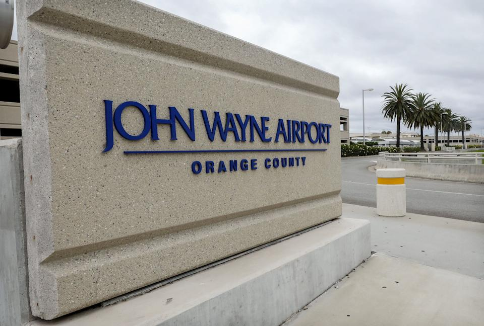 SANTA ANA, CALIFORNIA - JUNE 28: A sign is displayed at John Wayne Airport, located in Orange County, on June 28, 2020 in Santa Ana, California. Orange County Democrats are calling for the name of the airport to be changed due to the deceased actor's history of 'racist and bigoted statements'. (Photo by Mario Tama/Getty Images)