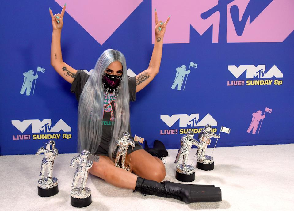 """Post-show, Gaga posed with her five VMAs in an oversized T-shirt by Haus of Gaga. Her mask, which was designed by Michael Ngo, gave the look an edgier touch.<br><br><em>Lady Gaga is wearing an MTV VMAs x Chromatica T-shirt by Haus of Gaga, a Michael Ngo mask, and Pleaser shoes.</em><br><br><br><br><span class=""""copyright"""">Photo: Kevin Winter/Getty Images.</span>"""