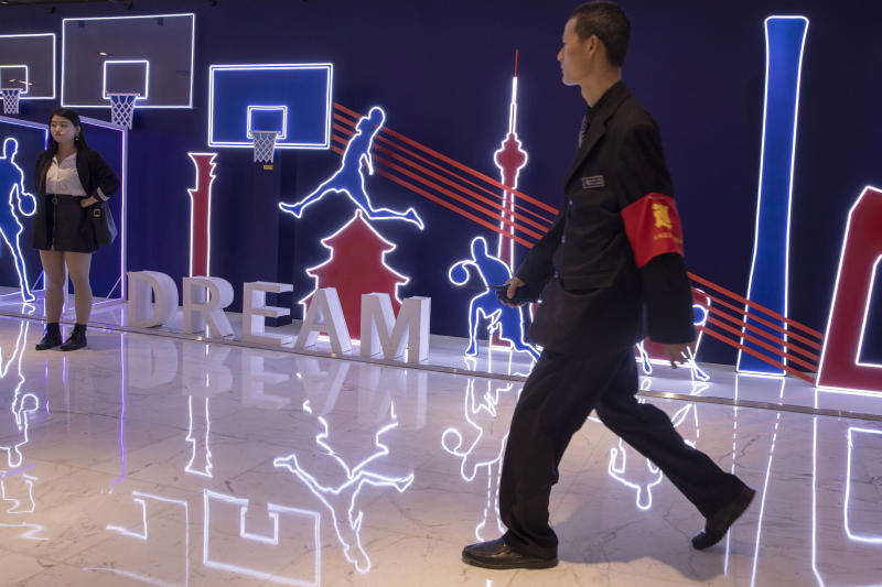 """In this Friday, Oct. 11, 2019, photo, a security guard walks past neon light decor depicting basketball players and silhouette of iconic Chinese buildings in Beijing. When Houston Rockets' general manager Daryl Morey tweeted last week in support of anti-government protests in Hong Kong, everything changed for NBA fans in China. A new chant flooded Chinese sports forums: """"I can live without basketball, but I can't live without my motherland.""""(AP Photo/Ng Han Guan)"""