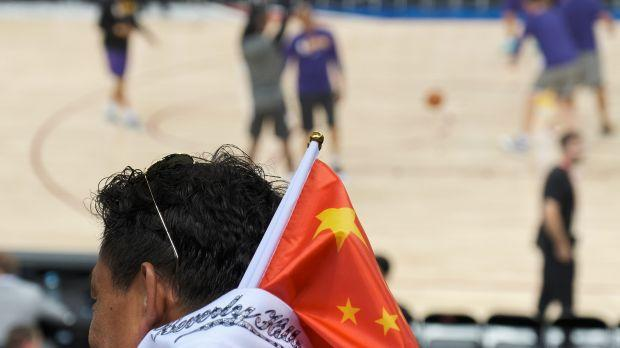 A fan carries a Chinese national flag during an NBA Los Angeles Lakers v Brooklyn Nets game in Shenzhen, China on October 12, 2019.