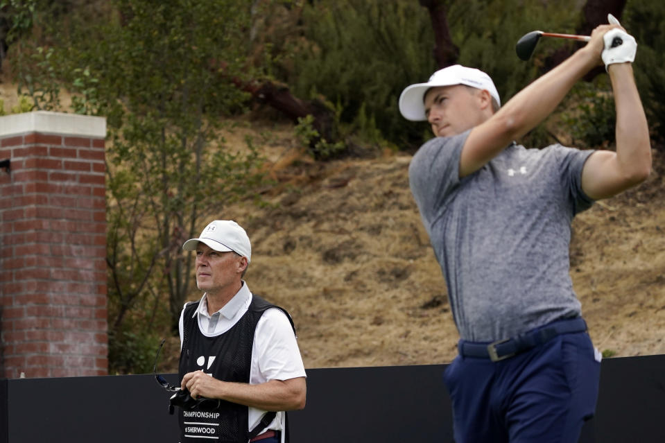 Shawn Spieth, left, caddies for his son Jordan Spieth, teeing off, during the first round of the Zozo Championship golf tournament Thursday, Oct. 22, 2020, in Thousand Oaks, Calif. (AP Photo/Marcio Jose Sanchez)
