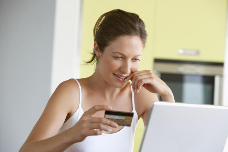 Woman at a laptop with a credit card in hand