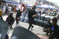 Anti-coup protesters practice a defense formation with makeshift shields during a demonstration in Yangon, Myanmar, Saturday, March 13, 2021. Security forces in Myanmar on Saturday again met protests against last month's military takeover with lethal force, killing at least four people by shooting live ammunition at demonstrators. (AP Photo)