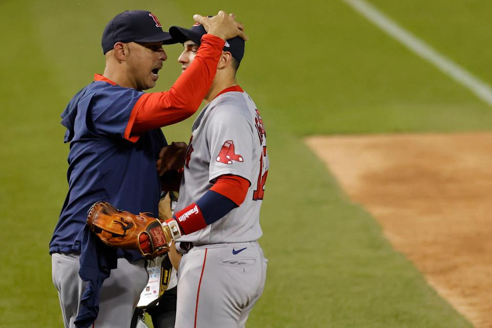 Red Sox manager Alex Cora, left, celebrates with Jose Iglesias after clinching a wild card berth on Sunday.