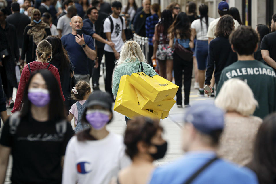 FILE - In this Monday, June 15, 2020 file photo people walk with bags after shopping at the Selfridges department store in London. (AP Photo/Matt Dunham, File)