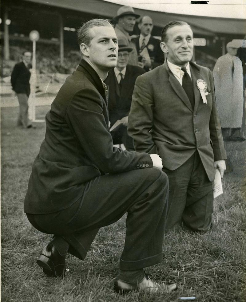 The Duke of Edinburgh at the White City watching a relay race. With him is Lord Burghley - Credit:  AP