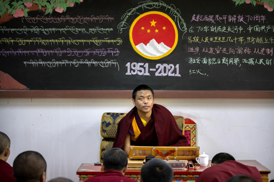 A monk teaches a class while sitting beneath a chalkboard with a mural commemorating the 70th anniversary of the Chinese government's control of Tibet at the Tibetan Buddhist College near Lhasa in western China's Tibet Autonomous Region, Monday, May 31, 2021, as seen during a government organized visit for foreign journalists. High-pressure tactics employed by China's ruling Communist Party appear to be finding success in separating Tibetans from their traditional Buddhist culture and the influence of the Dalai Lama. (AP Photo/Mark Schiefelbein)