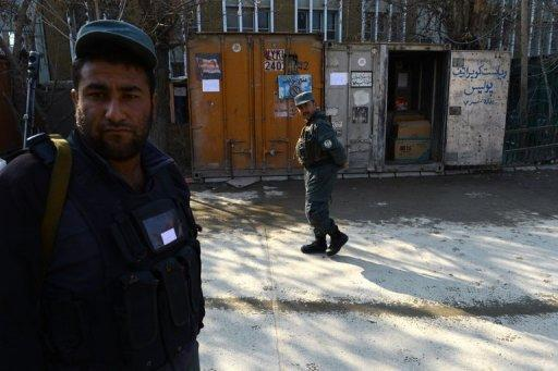 Afghan police stand guard at the site where a female police officer shot dead a foreign adviser on December 24, 2012