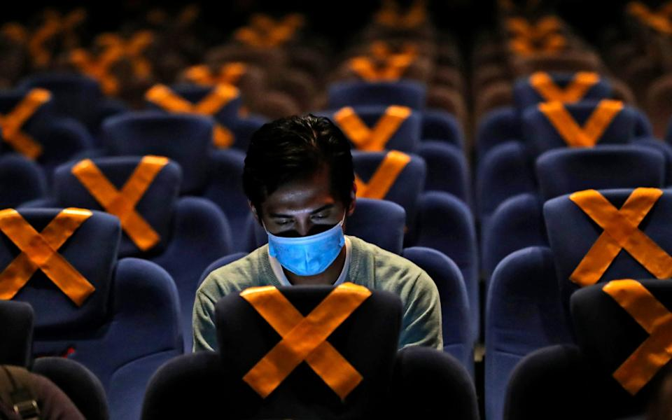 A man checks his mobile phone as he sits amid physical distancing markers prior to the start of a movie at CGV Cinemas theater in Jakarta, Indonesia - AP