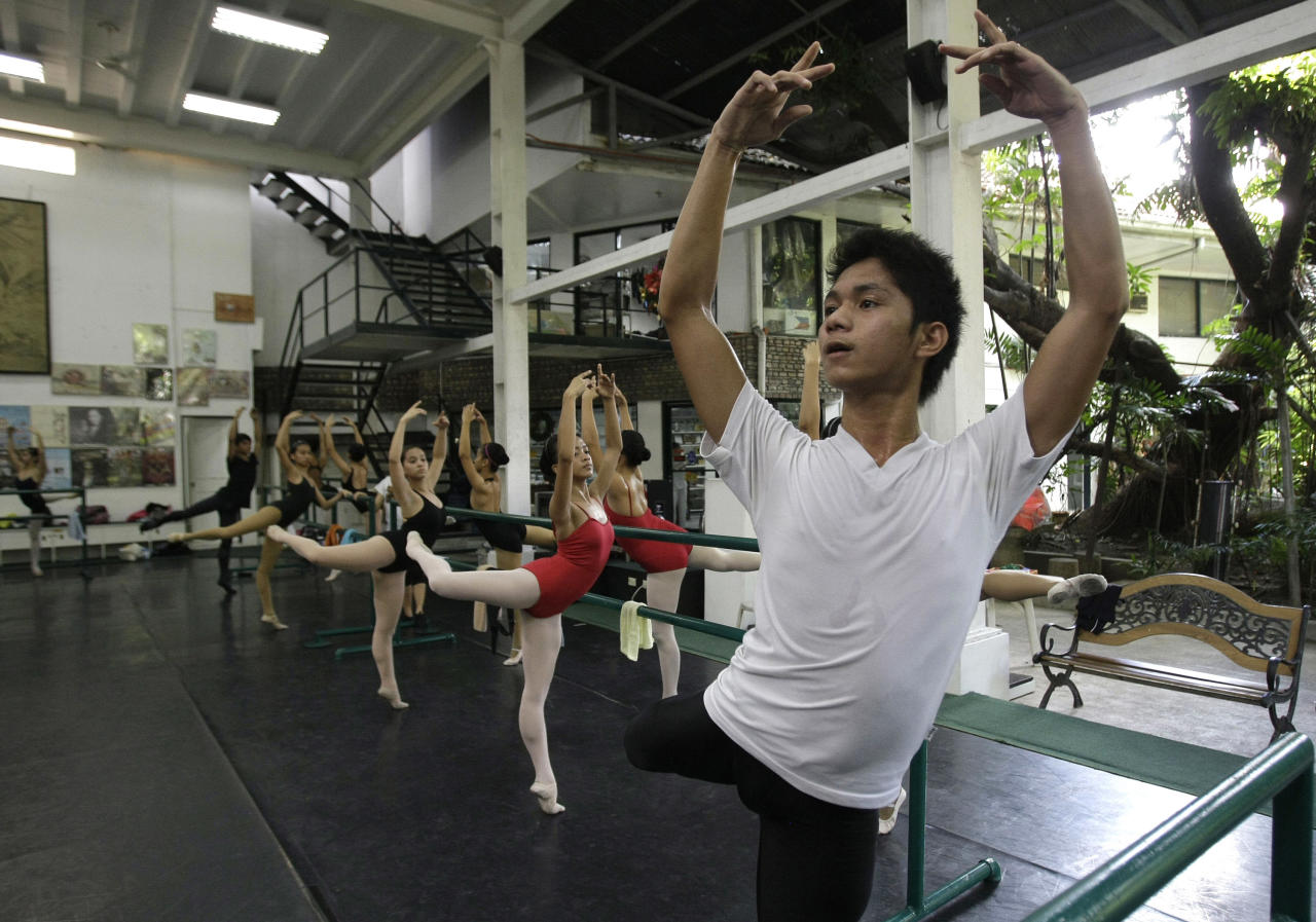 In this photo taken Nov. 25, 2012, Filipino slum dweller Jamil Montebon, right, focuses during a class at Ballet Manila at the Philippine capital. Montebon, a scholar at Ballet Manila's program, used to collect garbage and also worked at a junk shop. He now receives a monthly stipend, stays at their dormitory and given meals. (AP Photo/Aaron Favila)