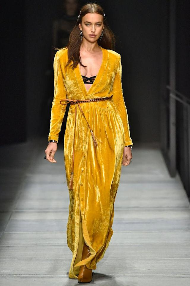 <p>Model Irina Shayk wears a yellow velvet wrap dress at the Bottega Veneta FW18 show. (Photo: Getty) </p>