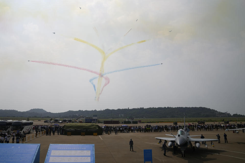 """Members of the """"August 1st"""" Aerobatic Team of the Chinese People's Liberation Army (PLA) Air Force perform near the J-10C on display during the 13th China International Aviation and Aerospace Exhibition, also known as Airshow China 2021, on Tuesday, Sept. 28, 2021 in Zhuhai in southern China's Guangdong province. (AP Photo/Ng Han Guan)"""