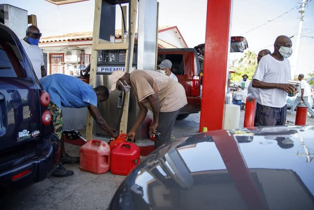 Residents fill their containers with petrol at Cooper's petrol station before the arrival of Hurricane Isaias in Freeport, Grand Bahama, Bahamas (Tim Aylen/AP)