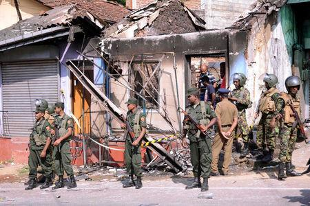 Sri Lanka's Special Task Force and Police officers stand guard near a burnt house after a clash between two communities in Digana, central district of Kandy, Sri Lanka March 6, 2018. REUTERS/Stringer