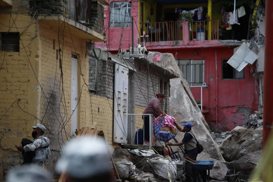 Residents evacuate from their home at the site of a landslide that brought tons of massive boulders down on a steep hillside neighborhood, in Tlalnepantla, on the outskirts of Mexico City, Saturday, Sept. 11, 2021. A section of the peak known as Chiquihuite gave way Friday afternoon, plunging rocks the size of small homes onto the densely populated neighborhood. (AP Photo/Ginnette Riquelme)