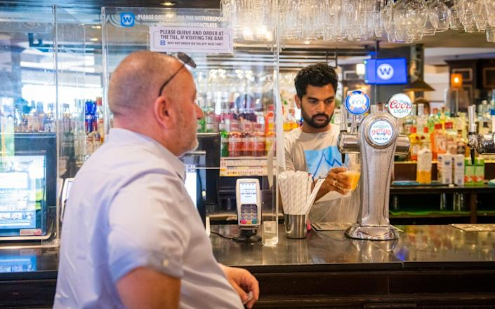 A pub-goer orders a pint at the bar in Bournemouth - Vagner Vidal/Hyde News & Pictures Ltd