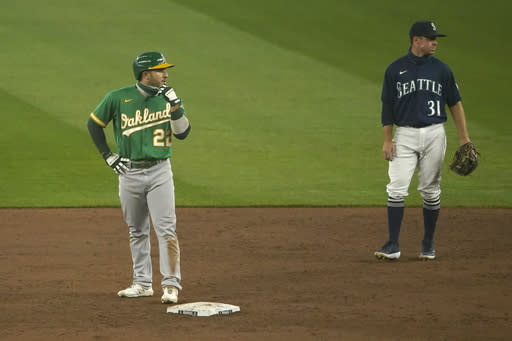 Oakland Athletics' Ramon Laureano, left, stands on second base next to shortstop Donovan Walton (31) after hitting a two-run double during the third inning of the second baseball game of a doubleheader, Monday, Sept. 14, 2020, in Seattle. (AP Photo/Ted S. Warren)