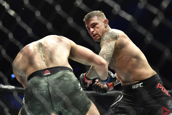 Dustin Poirier punches Conor McGregor in a lightweight fight during the UFC 257 main event. (Photo by Chris Unger/Zuffa LLC)
