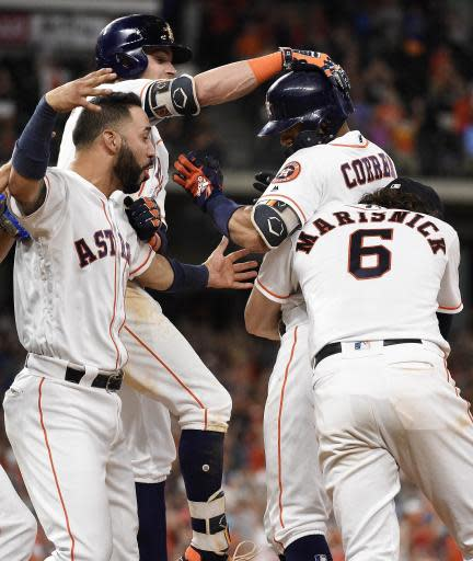 Houston Astros' Carlos Correa, second from right, celebrates his walkoff RBI-single to win the game with, from left to right, Marwin Gonzalez, Josh Reddick and Jake Marisnick during the twelfth inning of a baseball game against the Kansas City Royals, Saturday, June 23, 2018, in Houston. (AP Photo/Eric Christian Smith)
