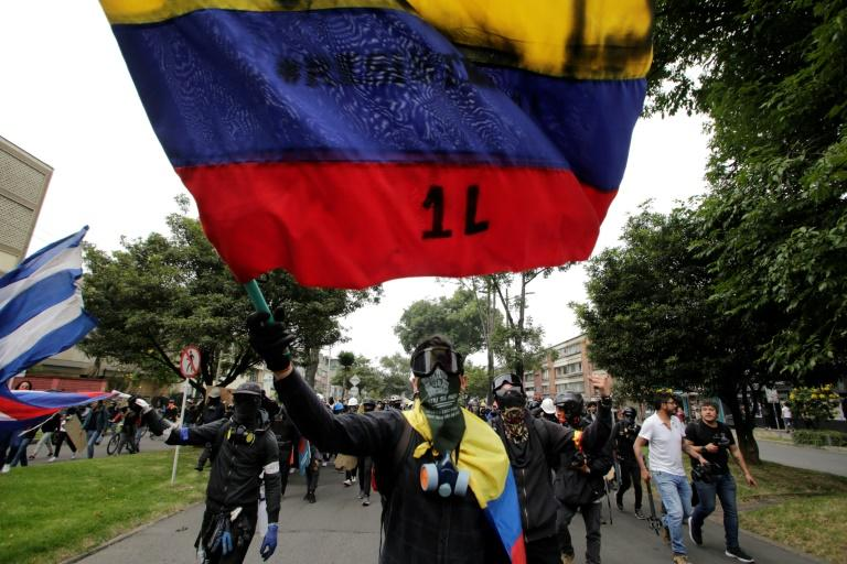 Protesters with their faces covered wave flags during a demonstration against the government of Colombia's President Ivan Duque in Bogota